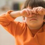 Мальчик трет глаза грязными руками